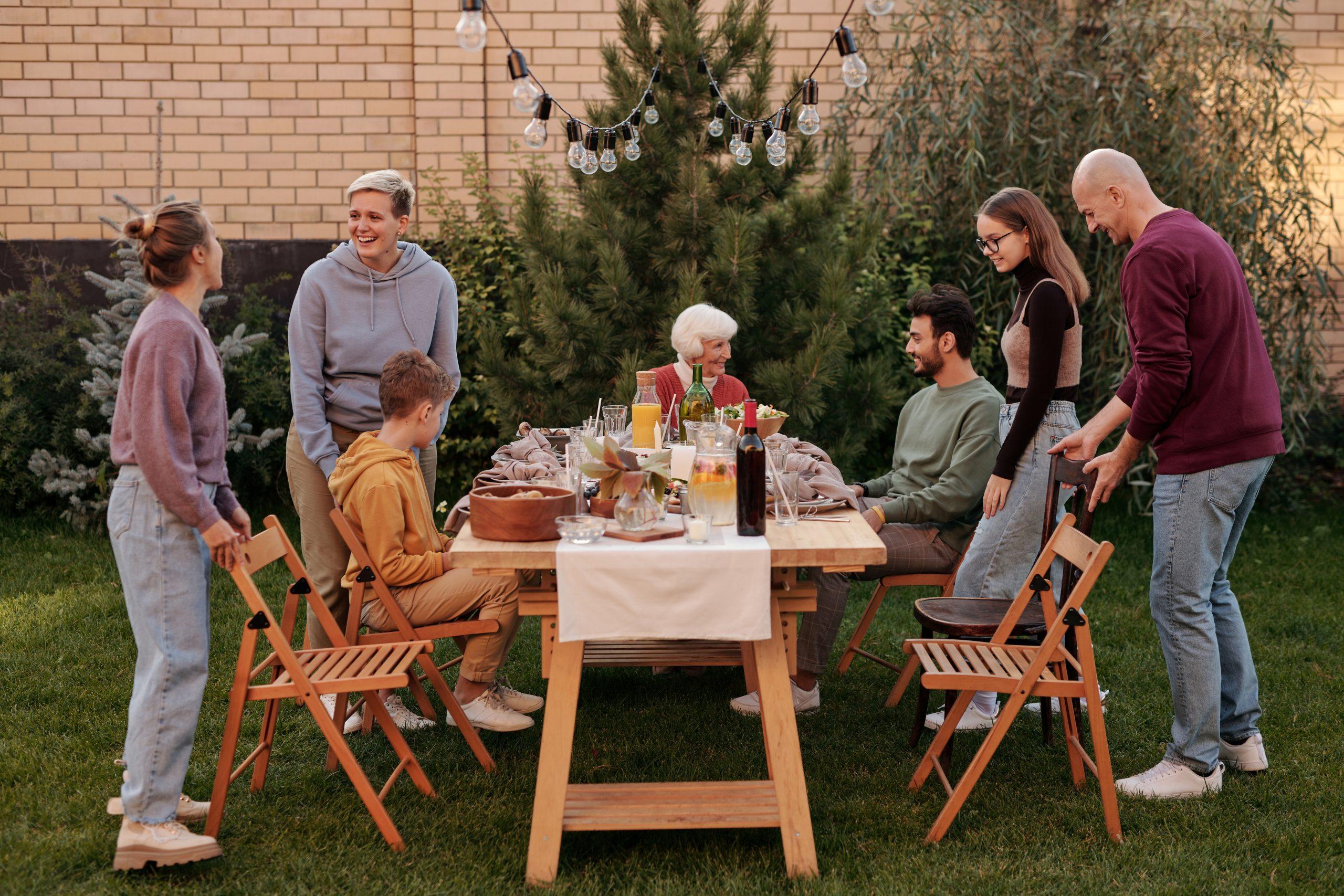 Ryhmä ihmisiä katetun puutarhapöydän ympärillä