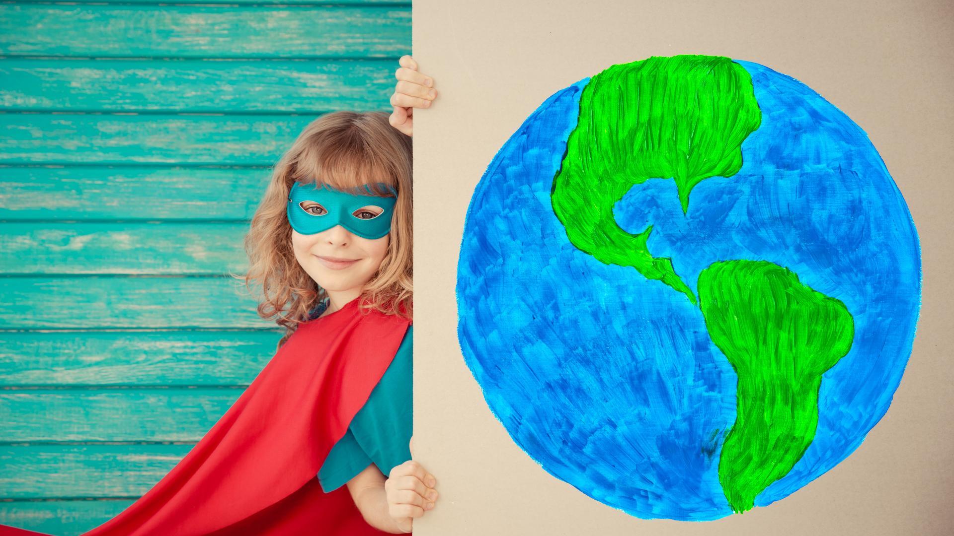 Sankariksi pukeutunut tyttö pitää pahvista maapallonkuvaa käsissään.