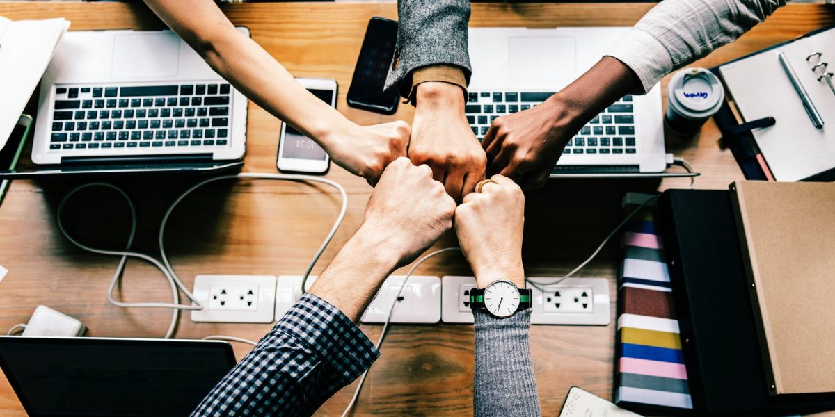 A photo of five hands together over an office table.